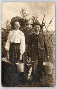 RPPC Worn Faces of Farmer & Wife Scooping Berries Into Buckets~Split Rail c1910