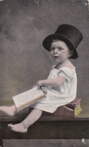 BIRTHDAY, PU-1909; Toddler wearing top hat sitting on a book