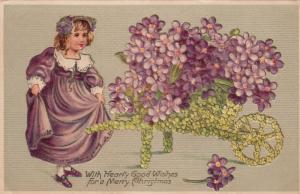 Merry CHRISTMAS; 00-10s; Girl in purple dress, cart of purple flowers
