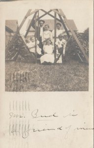 RP: ST. LOUIS , Missouri , 1910 ; Family posed on a swing
