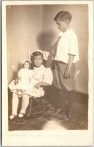 Vintage RPPC Real Photo Postcard Little Girl in Chair w/ Doll & Awkward Brother