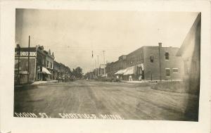 Chatfield  MN Undertaker~Man Carries 2 Bags of Feed~Main Street Sepia RPPC 1911