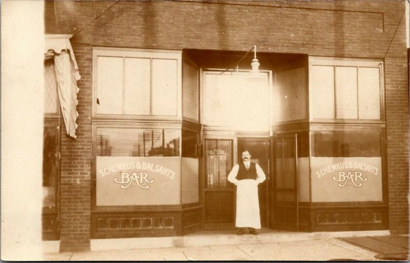 Schemkus & Bahlsat Bar~Storefront~Owner Wearing A Bartender's Apron c1910 RPPC