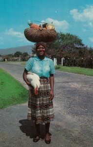 JAMAICA , W.I. 1950-60s; Woman returning from market, carrying a chicken