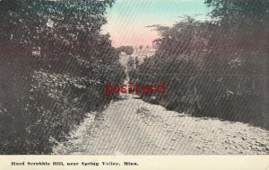 1910? SPRING VALLEY MN HARD SCRABBLE HILL very rocky dirt road, blgs in distance