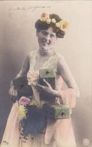 Lovely woman wearing a sleeveless lace gown holding presents, flowers in her ...