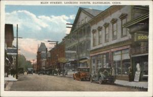 Danielson CT Main St. South c1920 Postcard Cars Store Signs