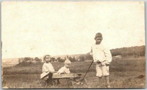 c1910s RPPC Real Photo Postcard Boy Pulling Brother & Sister in Toy Wagon