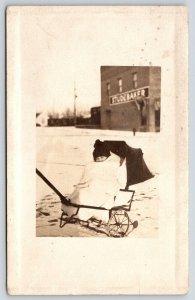 Real Photo Postcard~Baby in Wheel Barrow Pull Cart~Studebaker Building~1910 RPPC