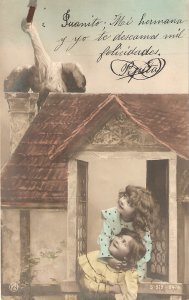 Boy and girl looking at stork in the roof Nice vintage  postcard