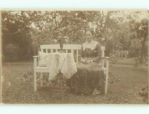 rppc 1920's WOMAN ON BENCH BESIDE FLOWER VASE ON STAND AC8878