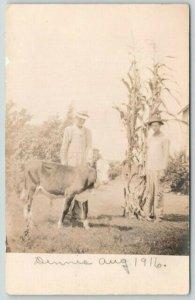 Real Photo Postcard~2 Farmers~Cow~Dennis~Big Overalls~2 10 Foot Cornstalks~1916