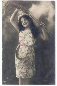 RP  Woman hold wheat over her head, scythe in waist band, 1910s