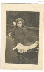 RP; Girl standing next to baby buggie with doll inside, 10-20s