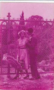 Tinted French RP: Man Holding Woman w/ Umbrella's Hand by Fence, 1920-30s