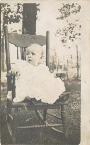 Distressed Baby Sitting In Wooden Rocking Chair~Real Photo Postcard c1913