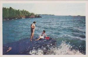 Man Admiring Woman in White Bathing Suit Lounging on Rock, Swim & Sun Time in...