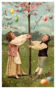 Easter , boy and girl shaking tree off eggs