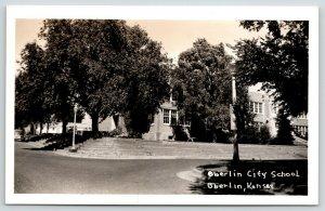 Oberlin KS~Curved Road Around City School~Terraced Stone Block Wall~RPPC c1950