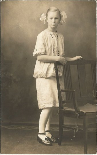 Real photograph postcard of Lovely young girl in pose next to chair in Sienna
