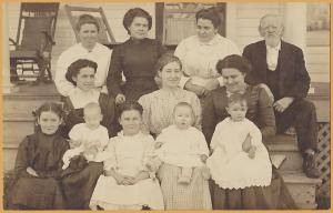 RPPC-Large family posing for portrait on front porch of house -