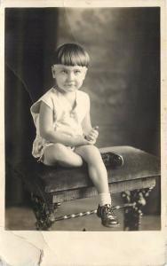 RPPC Postcard Little Boy with Bowl Cut Sitting on Bench Portrait