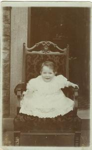 Infant sitting on chair, early 1900s unused real photo