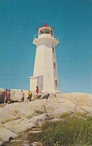 Canadian and American Tourists enjoy the beauty of Peggy's Cove, Lighthouse, ...