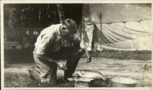 Man Camping Preparing Fish For Cooking c1920 Real Photo Postcard