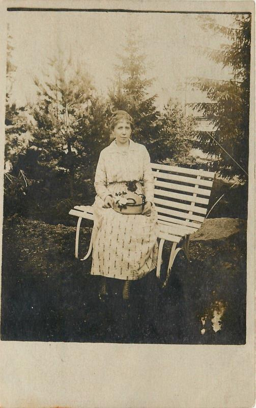 Woman On A White Wooden Bench, Holds Her Hat~Pine Trees Behind RPPC c1910