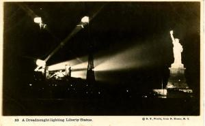 NY - New York City. Statue of Liberty lighted by USS New York - RPPC