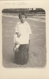 RP: Little girl in a white dress sitting on a log, 1900-10s
