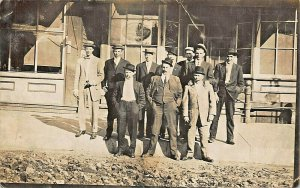 GROUP OF MEN -SUITS & HATS-FRONT OF EMPTY BUILDINGS-1900s REAL PHOTO POSTCARD