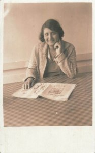 Postcard smiling lady reading newspaper photo