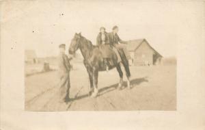 Real Photo Postcard~Couple Rides Side-Saddle on Huge Black Horse~Reins Man~c1911