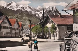 RP: Girl leading cow on street , Garmisch-Partenkirchen - Floriansplatz , Bav...