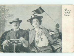 1905 WOMAN WAVES FLAG WHILE HUSBAND DRIVES VERY OLD CAR AB8307