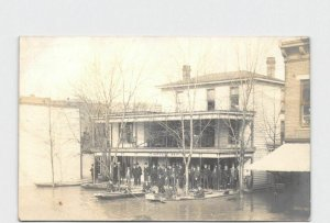 RPPC REAL PHOTO POSTCARD FLOOD MEN GATHERED ON PORCH OF HOTEL BRIT BOATS DOCKED