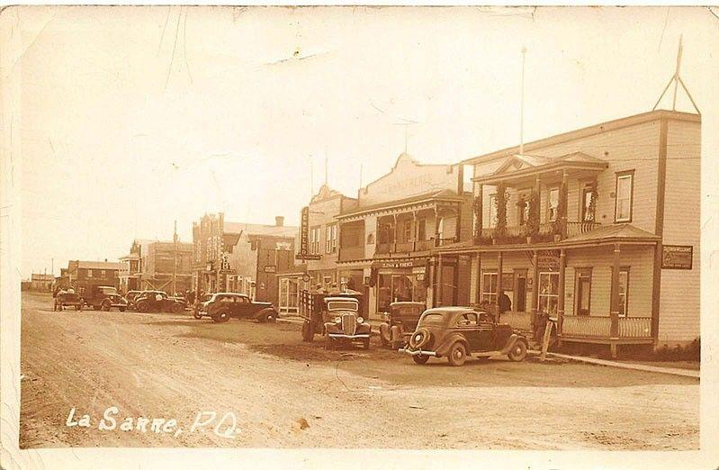 La Sarre Quebec Dirt Street Storefront Old Cars Truck in 1938 Real Photo PC