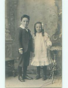 rppc 1920's GIRL WITH CURLS IN HER HAIR STANDS WITH BIG BROTHER AC8542