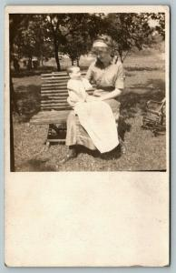 RPPC Young Lady on Bench Holds Realistic-Looking Baby Boy Doll on Her Lap c1910