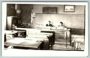 RPPC Two Teachers Grade Papers  in Empty Classroom~Globe on Piano~Inkwell~c1910