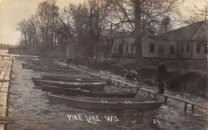 Pike Lake WI Man Stands by Rowboats in a Pen~Buildings Along the Shore~RPPC 1910
