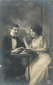Fancy couple playing cards