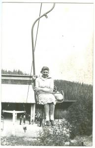Photo, Woman sitting in open chair lift, unknown location