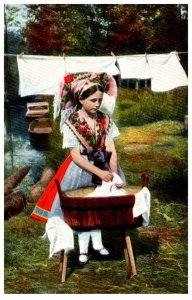 Young Girl washing clothes in wood bucket