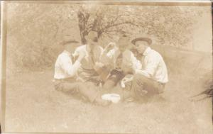 RP; Four men playing cards out in a field, 1910s