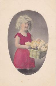 Cute little girl with blonde curly hair holding basket of carnation flowers, ...