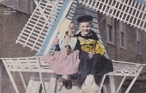 Dutch boy and girl sitting on miniature windmill, Tulip time at Holland, Mich...