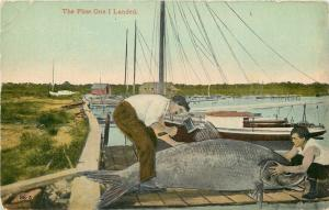 Exaggerated Fish~The First One I Landed~Two Men With Hatchet on Boat Dock~1910